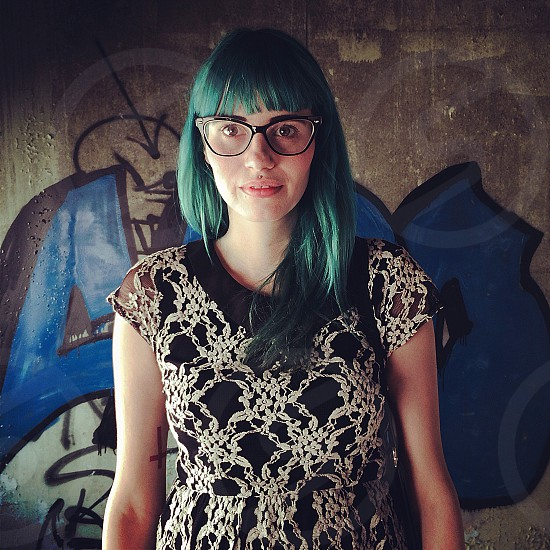 green-haired woman wearing black-rimmed eyeglasses and black white short-sleeve floral print dress photo