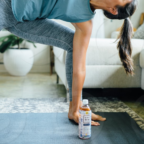 woman doing yoga at home while drinking tea photo