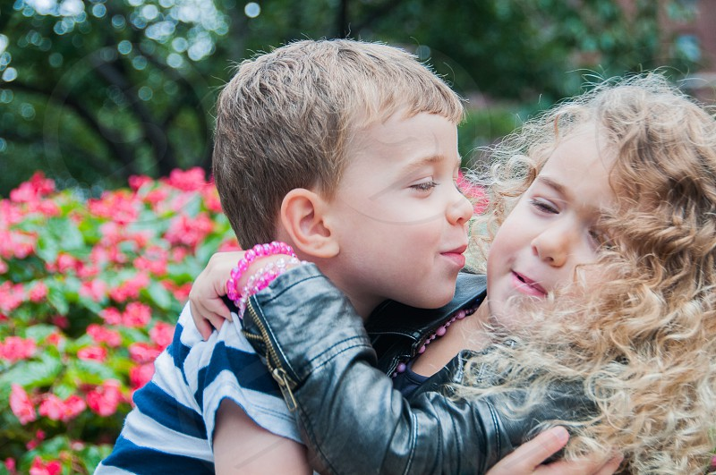 boy in blue and white stripe t shirt trying to kiss girl in black leather jacket photo