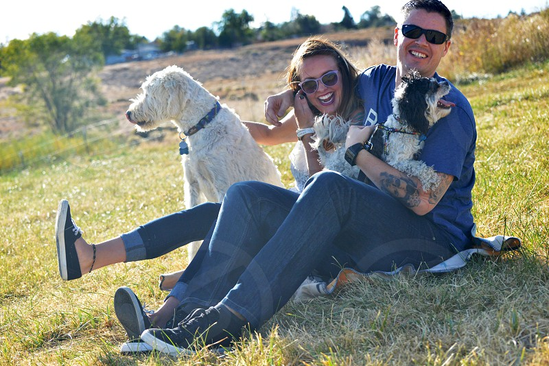 man and woman smiling together with 2 dogs photo