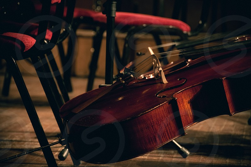 A cello propped against a chair on an empty stage. photo