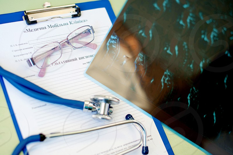 silver framed eyeglasses beside blue and grey sphygmomanometer photo