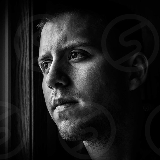 grayscale photo of man staring in window photo