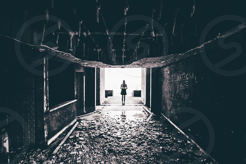 woman standing at distance in an abandoned building in grayscale photo