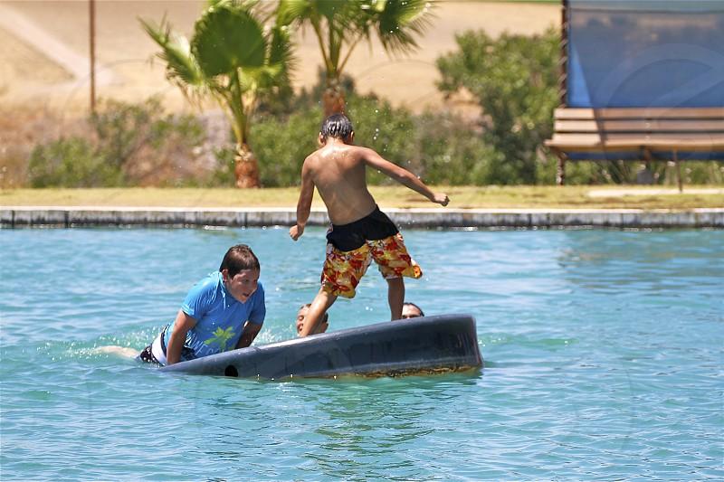 boys surfing on float photo
