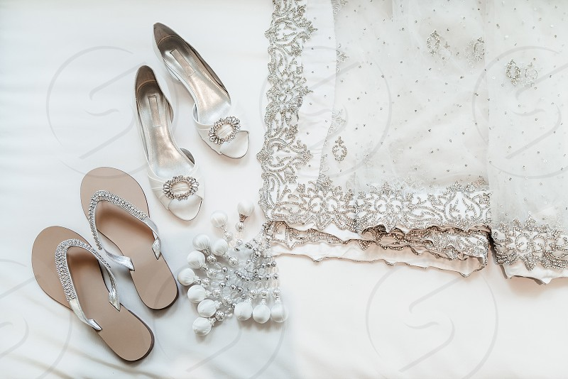 The pairs of shoes and luxury saree of the indian bride in white pastel theme on white background photo