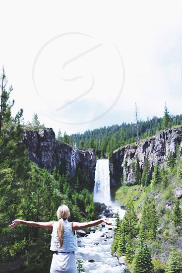 woman with arms wide open facing waterfalls nature photography photo