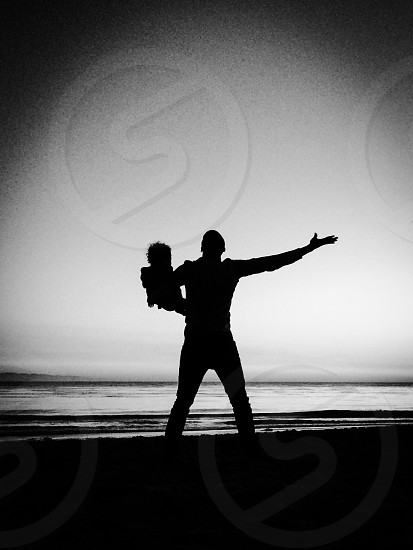 man holding baby by the ocean black and white photo  photo