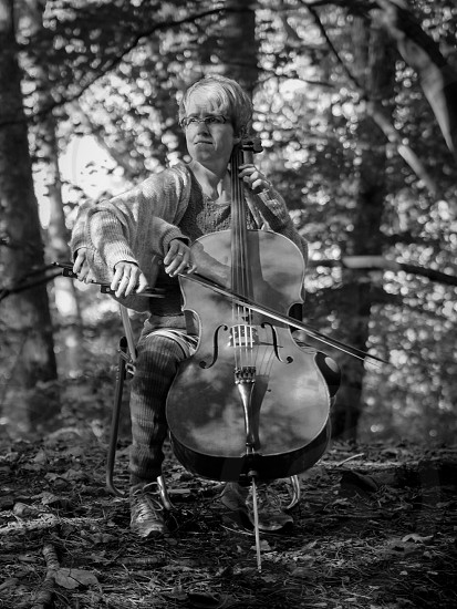 B&W portrait of a female Cellist playing her cello in the woods multiple exposure. photo
