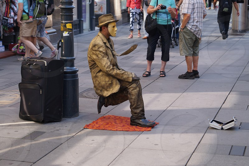 Magical man seating on the one leg like monument. photo