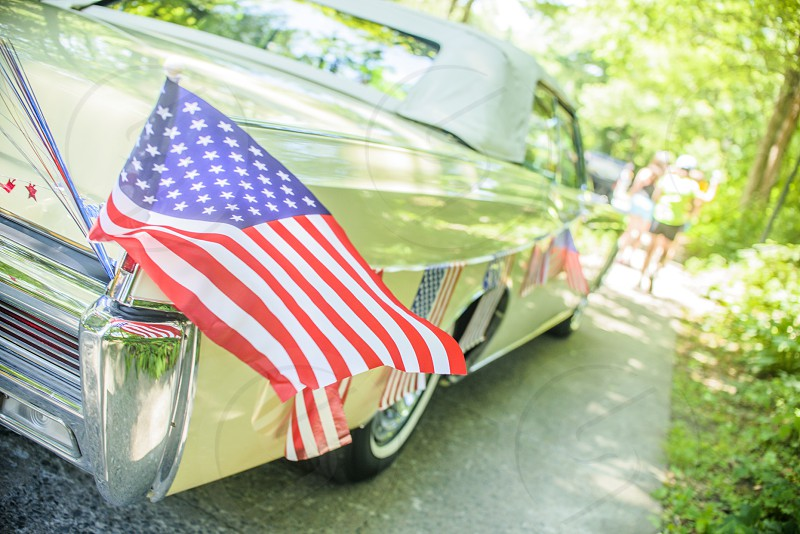 united states of america flaglet waving on the back of beige convertible classic car on paved road with person walking at distance near green plants during daytime photo