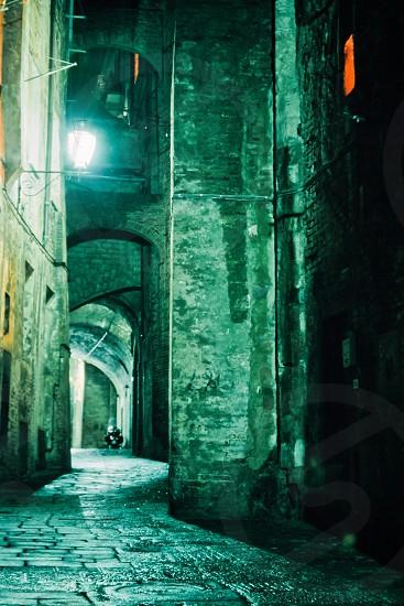 Ghostly illuminated narrow street in old medieval city of Siena at night Tuscany Italy Europe photo