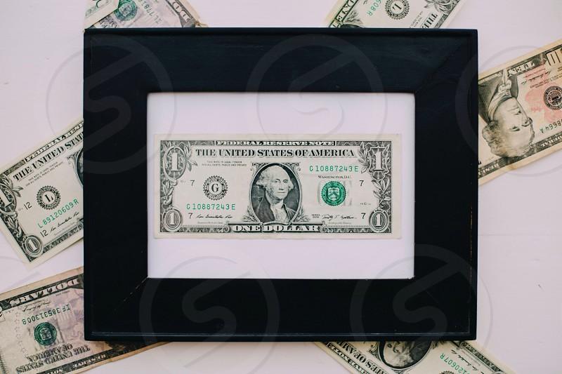 1 u.s dollar bill in black framed picture frame photo