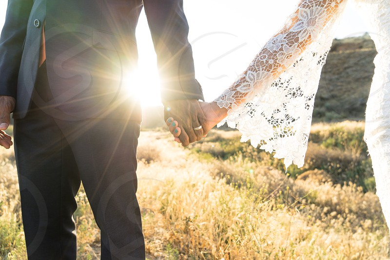 wedding couple holding hands and standing on green grass during daytime photo