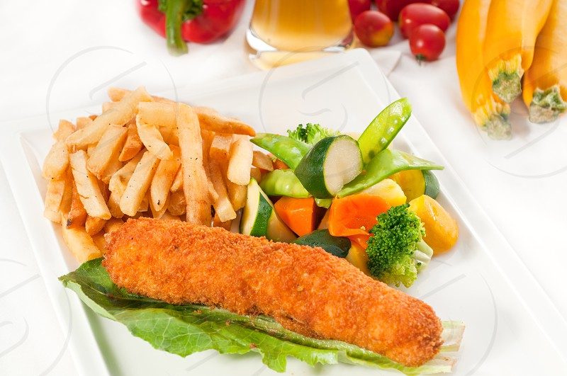 fresh breaded chicken breast roll and vegetableswith lager beer and fresh vegetables on background photo