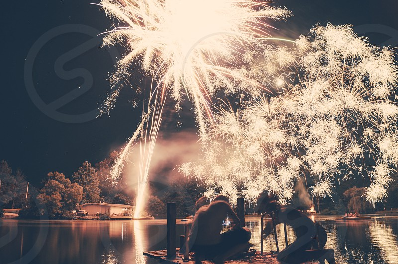 2 person on dock white lighting fireworks in the sky at night photo