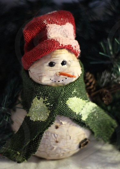 white snowman wearing red beanie hat and green scarf photo