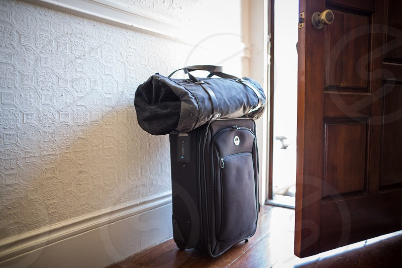 view of a blue luggage bag beside wooden door photo