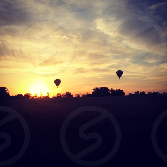 silhouette photo of two hot air balloons floating on sky during golden hour photo