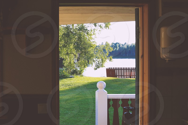 Cabin life view lakeside lake lawn indoors outdoors open door nature trees yard porch photo
