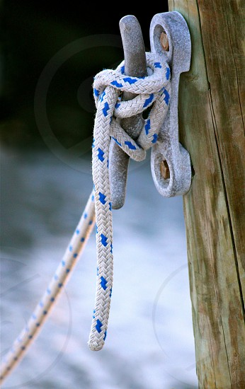 white and blue roped tied to post photo