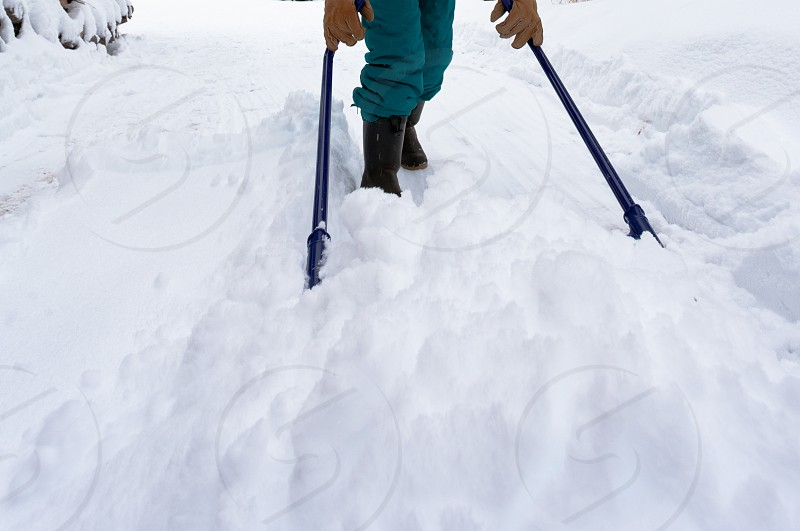 Manual snow removal from driveway using a snow scoop is good physical winter exercise. photo