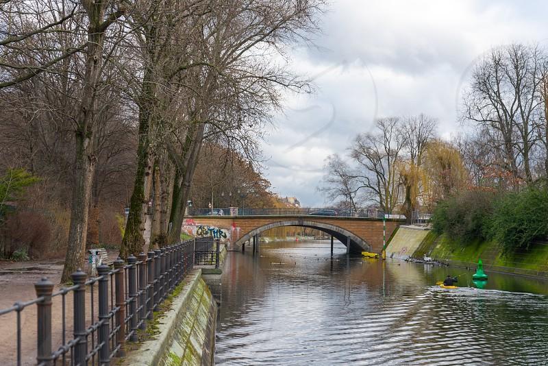 Landscape view and people's activities along Landwehr Canal inside Kreuzberg Neighborhood in Berlin Germany photo