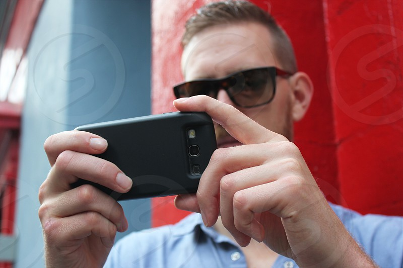30-yr old male filming on his mobile phone photo