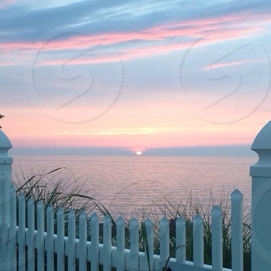 pink and blue sunset with white fence in the foreground photo