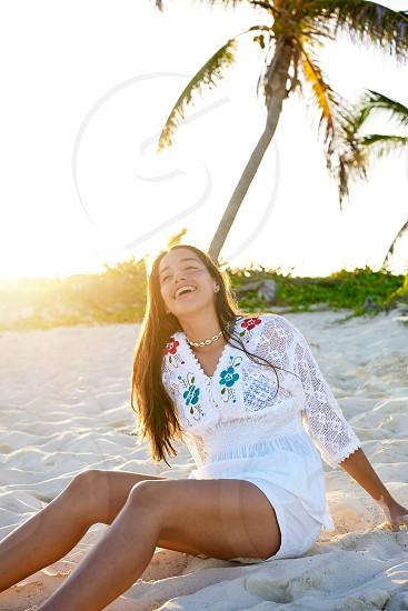 Latin beautiful girl sunset in Caribbean beach sand sitting relaxed photo
