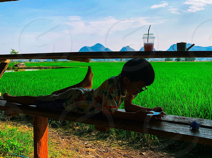 Boy looking phone in front of farm photo