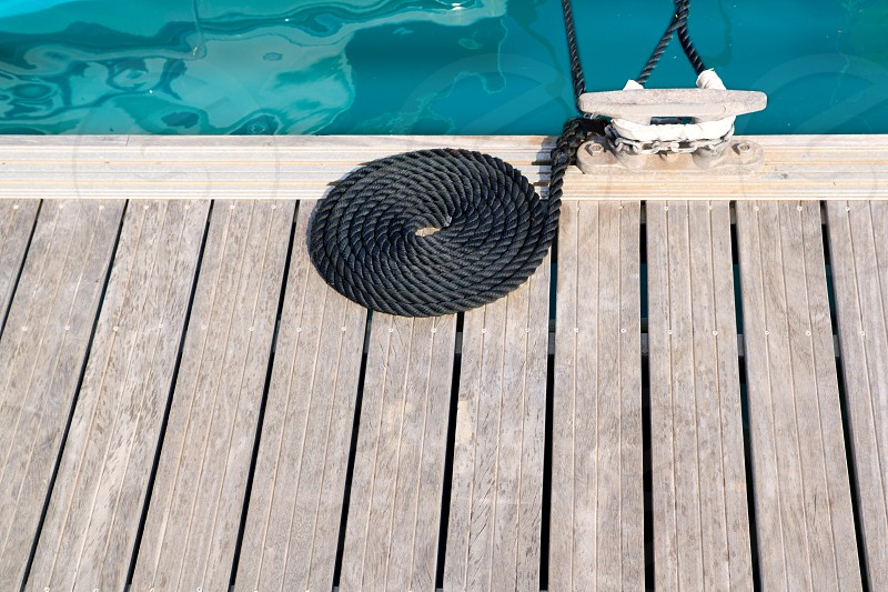 mooring wooden pier with coiled spiral rope and a bitt in marina photo
