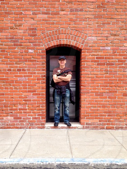 man in brown round neck t shirt standing near door photo