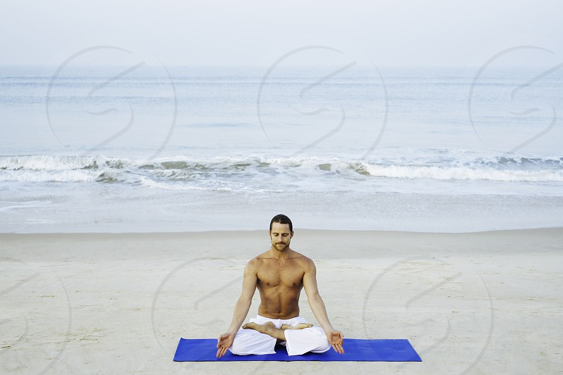 Young athletic man doing joga on the beach meditate in lotus posture padmasana photo