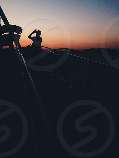 silhouette person taking photo of sunset photo