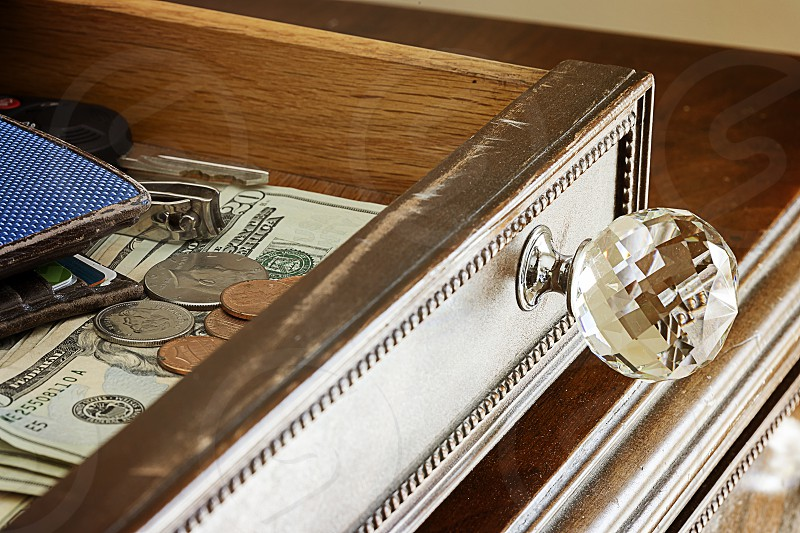 Money tossed in a dusty old drawer along with change wallet keys and nail clippers for safe keeping. photo