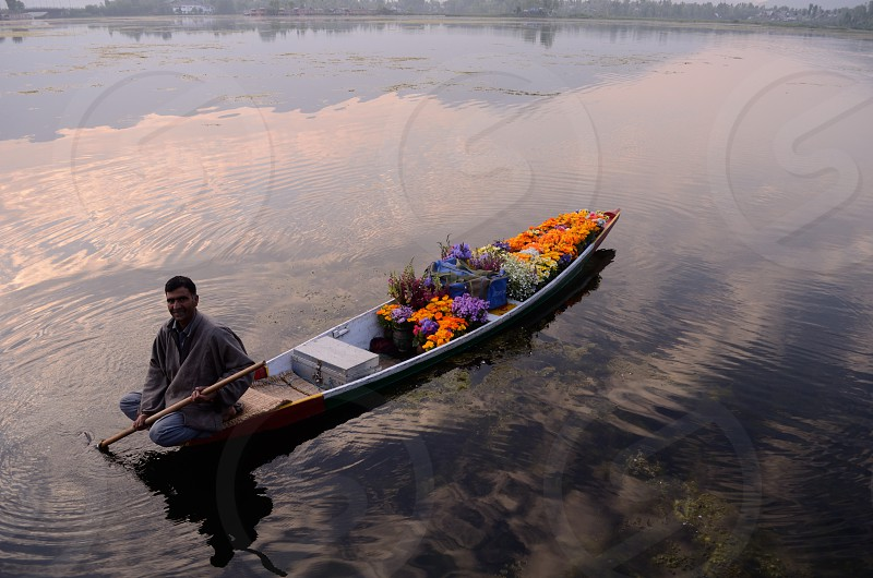 Reflections in the Nagin Lake in Kashmir India as a flower seller greets you in the morning  photo