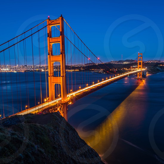 lights on the golden gate bridge at dusk time lapse photography photo