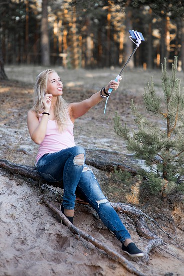 A woman taking a photograph or a selfie with a smart phone photo