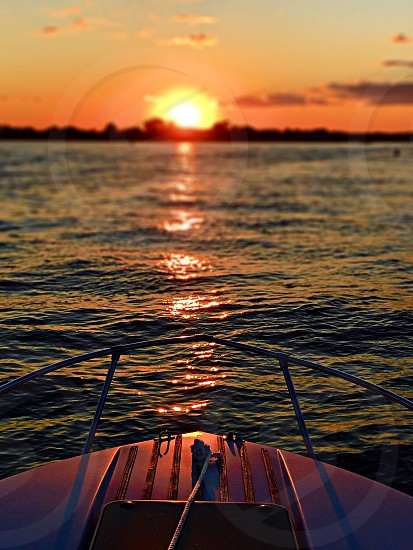 white and black boat on calm wave sea during sunset photo