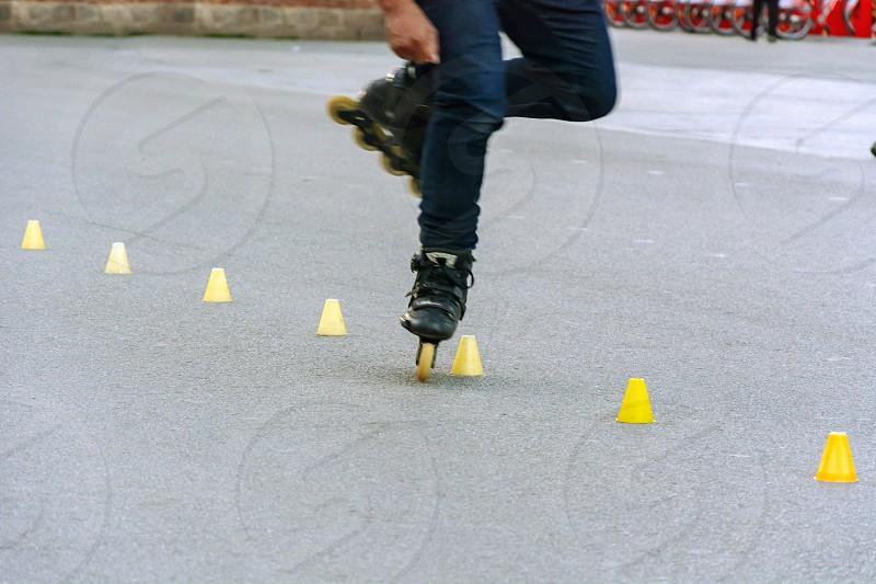 Feet of a skater while performing the slalom between yellow plastic cones placed in line on the asphalt photo