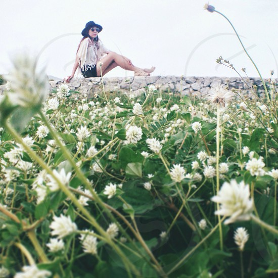 woman in black sunday hat in a meadow photo