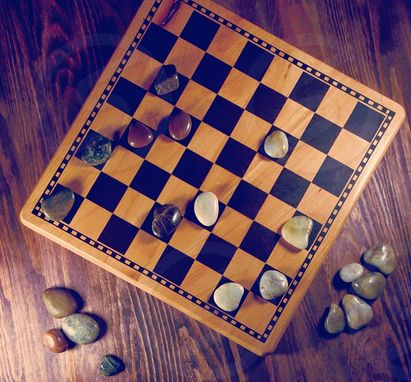 Classic Checkers Game board with light and dark rocks as checkers. photo
