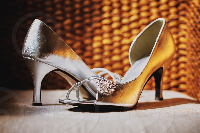 The women's shoes in silver color with glitter jewellry decoration on the cushion with reflection from the weave wooden photo
