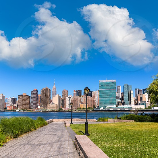Manhattan New York sunny skyline from green park turf East River NYC USA photo