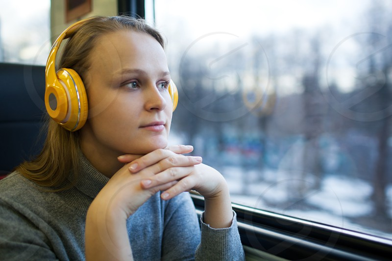 Thoughtful young woman in the train listening to music in wireless headphones and enjoying passing landscape from the window photo