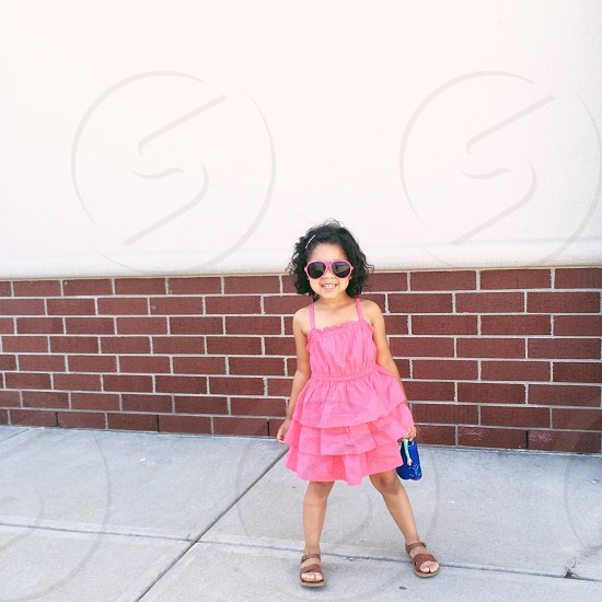 girl in pink dress standing and smiling photo