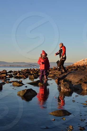2 people on grey rocky shore under blue sky during daytime photo