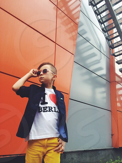 boy in i heart berlin t shirt and blue suit jacket standing against orange and black painted wall photo