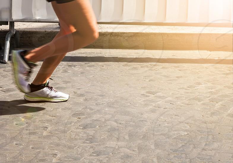 Marathon running race female feet on city cobblestone road photo